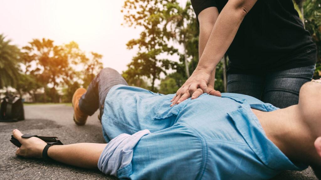 Erste Hilfe: Junger Mann im blauen Hemd liegt auf der Straße. Ein anderer Mann macht mit den Händen Herzdruckmassage.